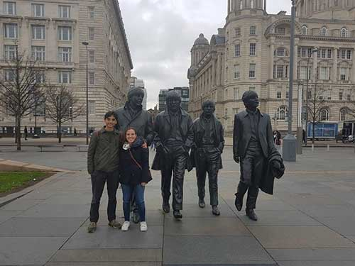 Juan Felipe Alvarez and a friends stood next to The Beatles statue in Liverpool