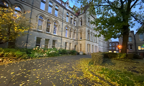 The University of Manchester building with yellow leaves on the road