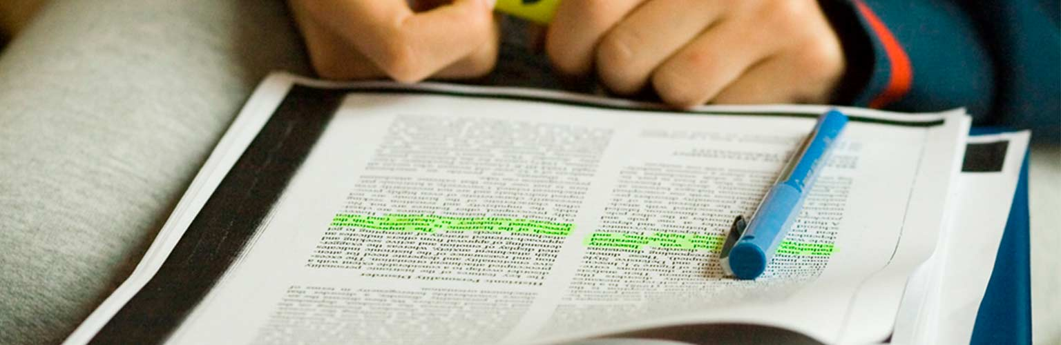 person highlighting text to revise for exam