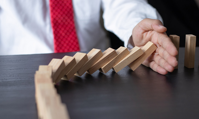 a businessman stopping the domino effect