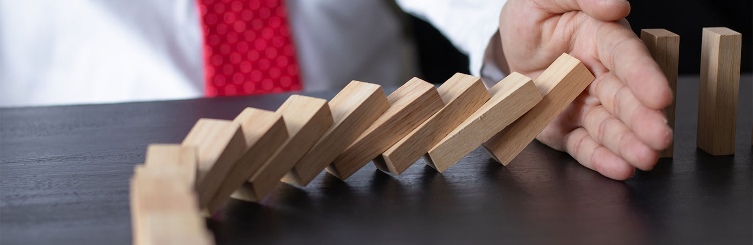 a businessman stopping domino effect