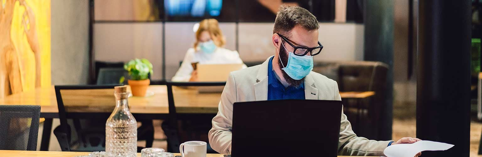 man working on a laptop wearing a facemask