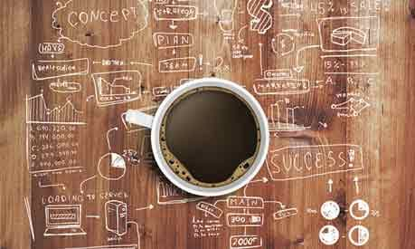 cup of coffee amongst strategy notes written on a table