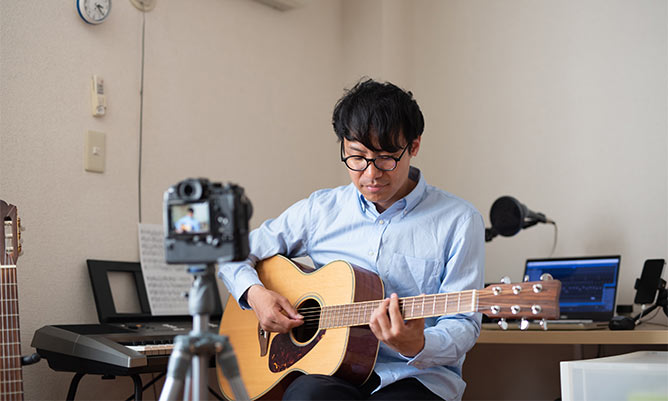 A man writing a song on his guitar
