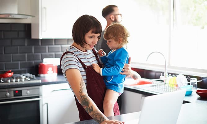 Mother holding child in kitchen young family