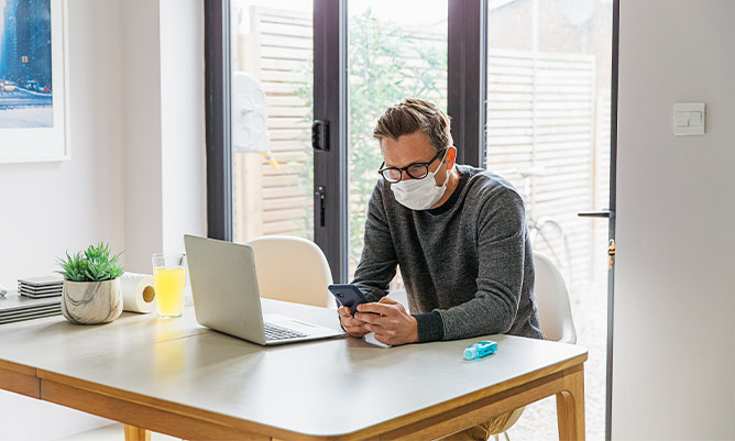 a man working from home with a face mask on