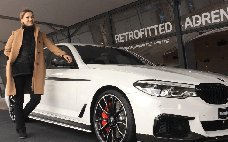 A woman standing next to a white sports car