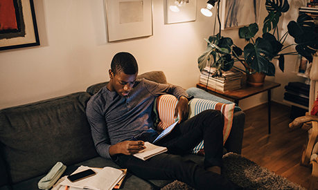 High angle view of a man using digital tablet while studying on sofa at home