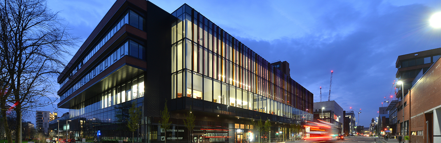 An image of the Alliance Manchester Business School building at night