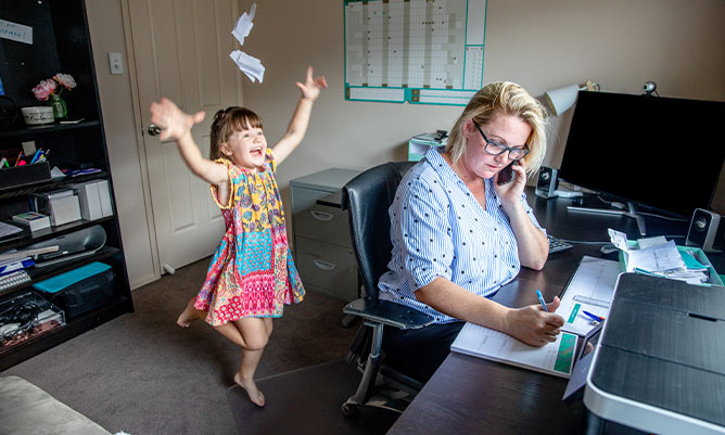 a woman attempting to work from home being distracted by her child