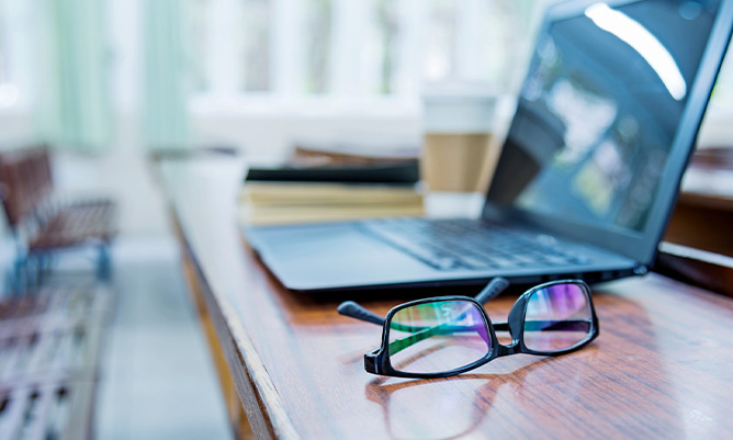 A pair of glasses and a laptop on a desk in an office