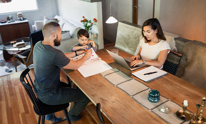 A woman working from home and a man is homeschooling his child