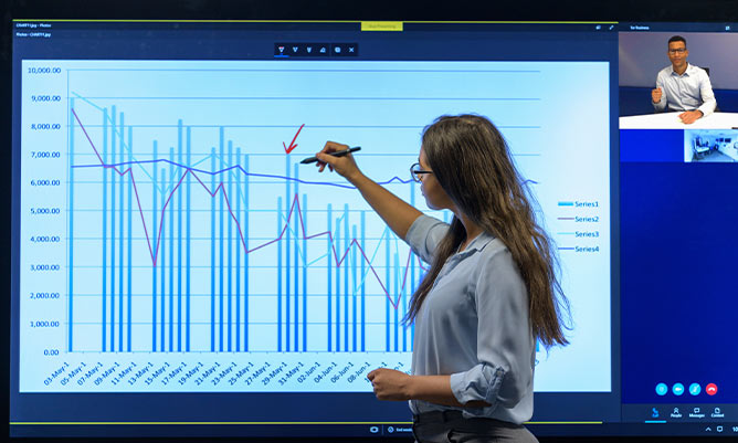 A business woman on a video conferencing call editing a graph