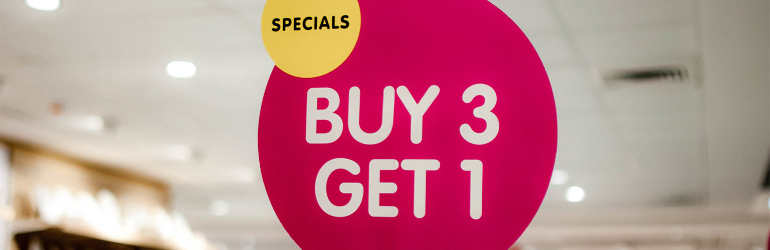 "A pink marketing ""buy 3, get 1"" sign"