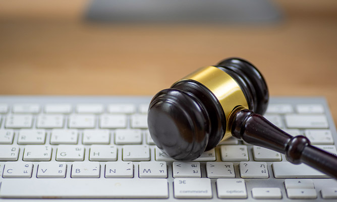 wooden gavel on computer keyboard