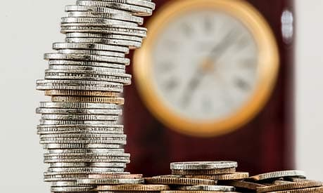 a pile of silver coins in the foreground and a clock in the background
