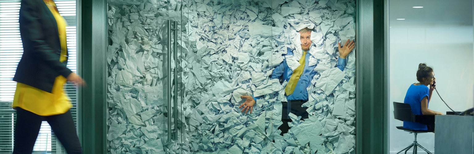 man squashed in office with too much paper