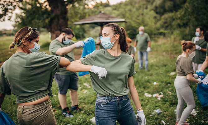 Group of volunteers with surgical masks cleaning nature together